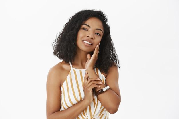 Tedere vrouwelijke en zachte jonge donkere vrouw zacht schoon gezicht aanraken met verrukking glimlachen