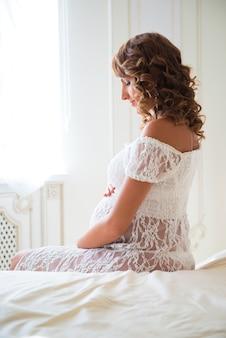Tedere zwangere vrouw zittend op bed en buik knuffelen