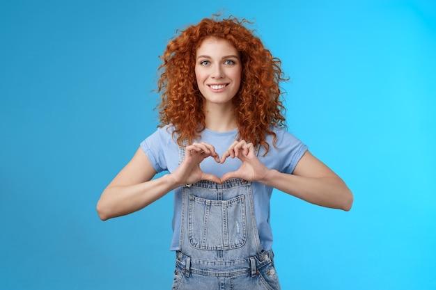 Tederheid, liefde, romantiek concept. mooie vrouwelijke schattige roodharige krullende vrouw toont hartgebaar borst uiten sympathie hartstochtelijke gevoelens glimlachend in het algemeen koesteren gevoelens staande blauwe achtergrond.