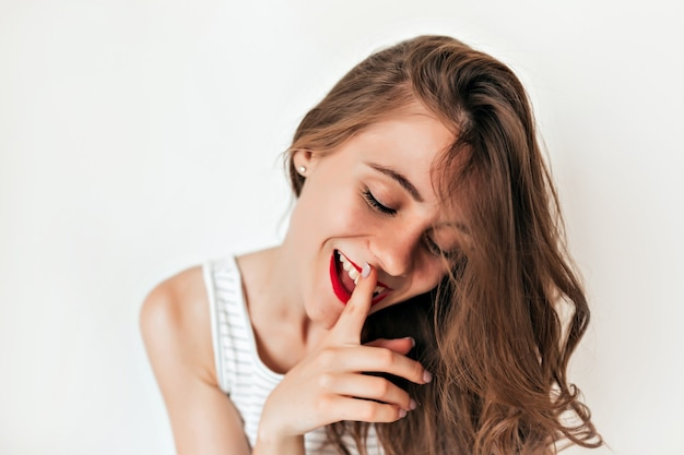 Tederheid mooie jonge vrouw met golvende haren en rode lippen legt een vinger op haar lippen