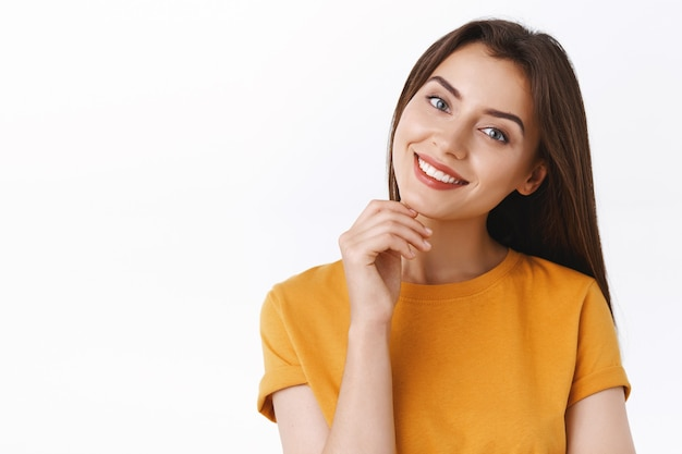 Tederheid, schoonheid en vrouwenconcept. sassy koket kaukasisch meisje in geel t-shirt, hoofd kantelen en vreugdevol glimlachen, kin zachtjes aanraken, sensualiteit en vrolijke emotie uitdrukken, witte achtergrond