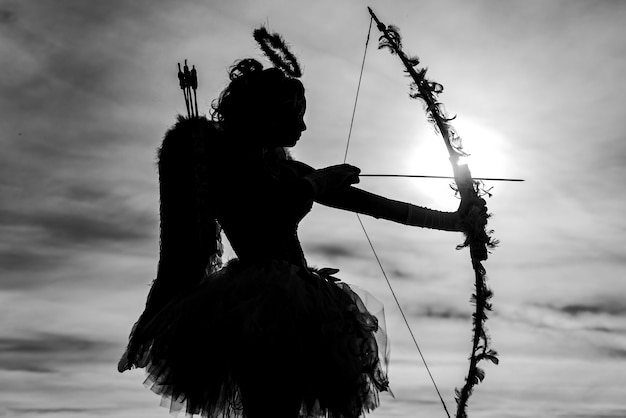 Teen angel girl archer op zonsondergang. silhouet van een cupido. leuke tienercupido op de wolk