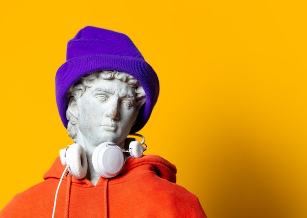Teen sculptuur in oranje hoodie en koptelefoon op gele achtergrond