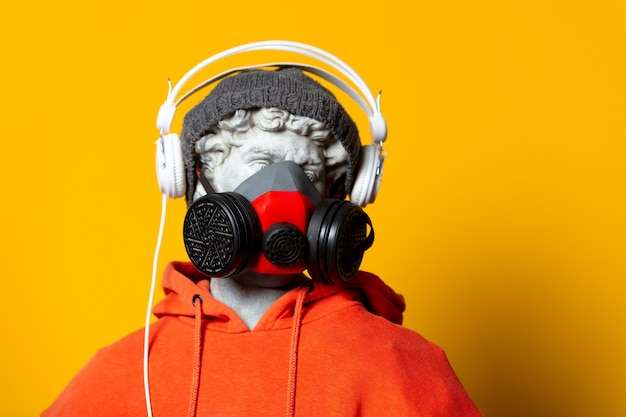 Teen sculptuur in oranje hoodie, gezichtsmasker en hoed met koptelefoon op gele achtergrond