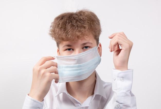 Teen zet een medisch masker op ter bescherming tegen het virus