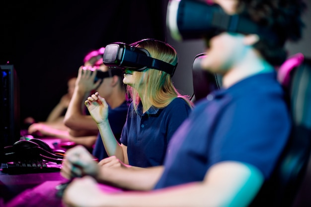 Teenage cybersports gamer in virtual reality goggle kijken en deelnemen aan netwerkvideospel met haar vrienden in de buurt