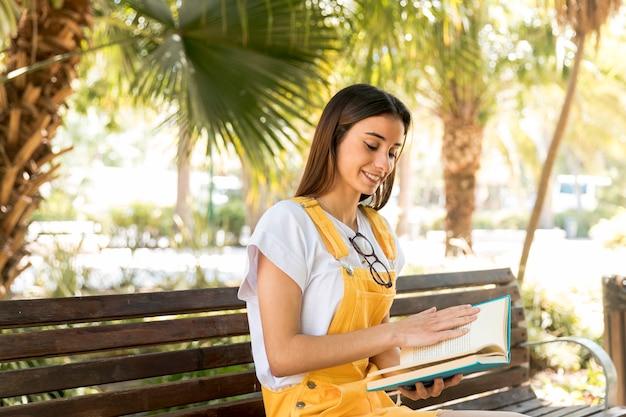 Teenage student leesboek op campus bankje