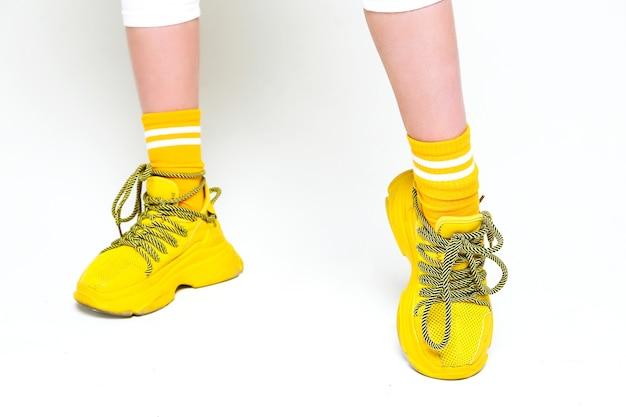 Teenage vrouwelijke benen in gele sneakers op een witte achtergrond. horizontale foto