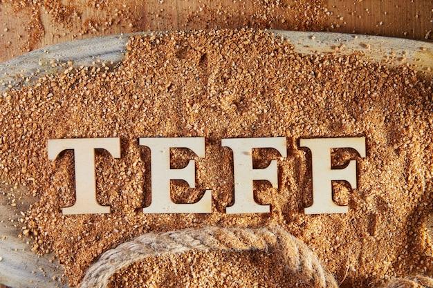 Teff, een alternatief voor oud glutenvrij graan met de naam geschreven in houten letters.