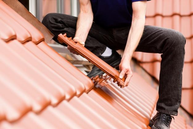 Tegelzetter die dak behandelt met nieuwe tegel