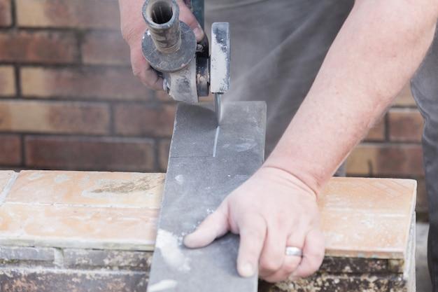 Tegelzetter die een tegel met een molen snijdt