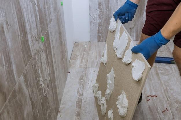Tegelzetter en gipsreparatiewerkzaamheden leggen van tegel, troffel in de hand van een man