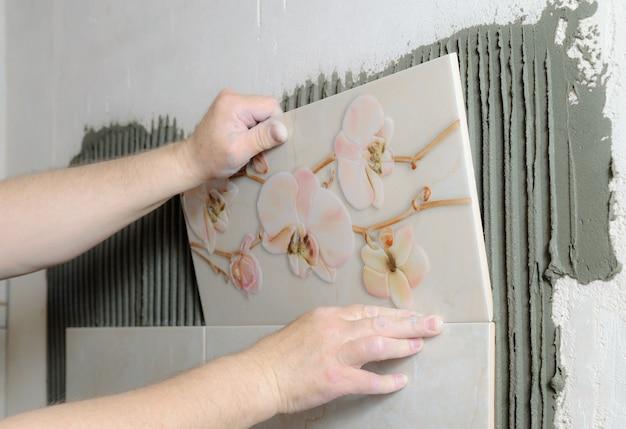Tegelzetters handen installeren een keramische tegel op een muur in een badkamer