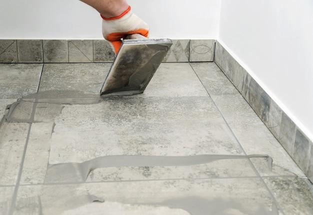 Tegelzetters vullen de ruimte tussen tegels met een rubberen troffel