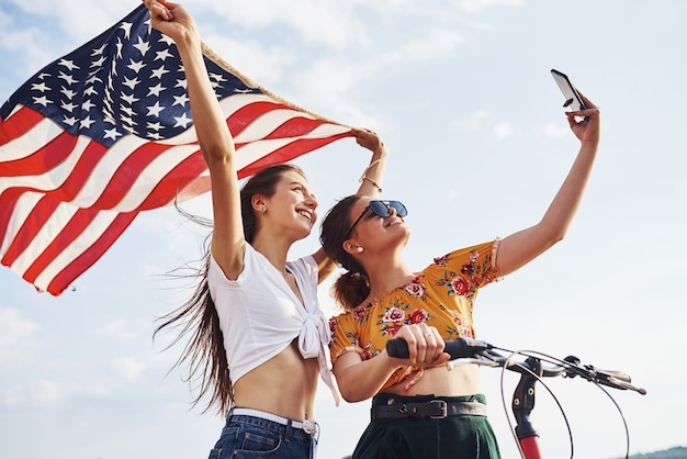 Tegen bewolkte hemel. twee patriottische vrolijke vrouw met fiets en usa vlag in handen maakt selfie.