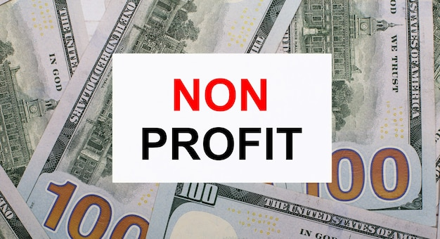 Tegen de achtergrond van amerikaanse dollars, een witte kaart met de tekst non profit. financieel concept