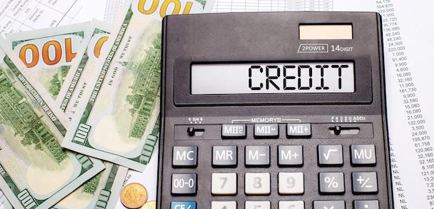 Tegen de achtergrond van contant geld en documenten staat een zwarte rekenmachine met de tekst credit op het scorebord. bedrijfsconcept