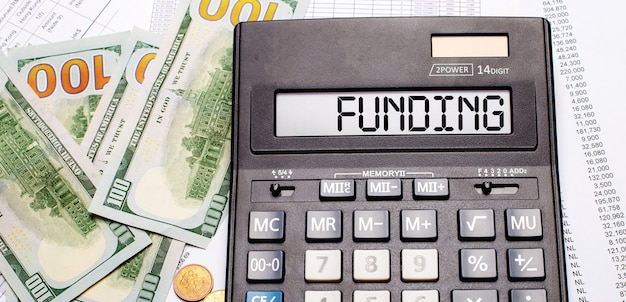 Tegen de achtergrond van contant geld en documenten staat een zwarte rekenmachine met de tekst funding op het scorebord. bedrijfsconcept