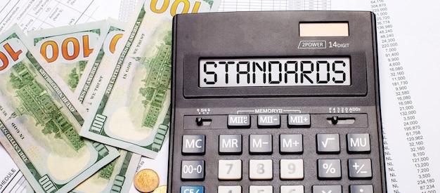 Tegen de achtergrond van contant geld en documenten staat een zwarte rekenmachine met de tekst standards op het scorebord. bedrijfsconcept