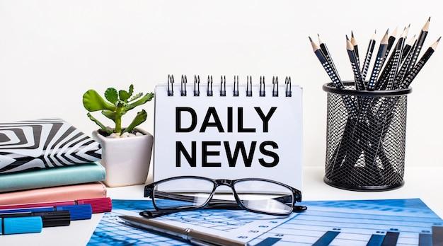 Tegen de achtergrond van een blauw schema en een witte muur, zwarte potloden in een standaard, een bloem, dagboeken en een notitieboekje met het opschrift daily news