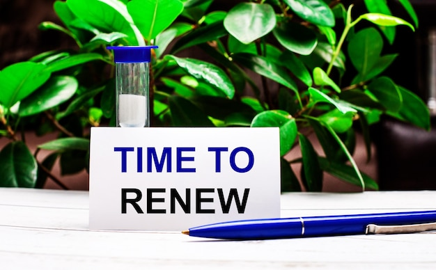 Tegen de achtergrond van groene bladeren van de plant staat een pen op tafel, een zandloper en een kaart met het opschrift time to renew