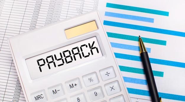 Tegen de achtergrond van rapporten en blauwe grafieken, een pen en een witte rekenmachine met een test op het payback-scherm. bedrijfsconcept