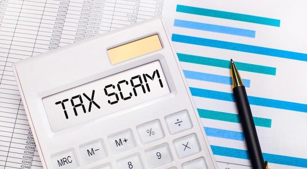 Tegen de achtergrond van rapporten en blauwe grafieken, een pen en een witte rekenmachine met een test op het tax scam-scherm. bedrijfsconcept