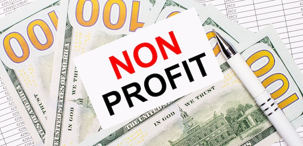 Tegen de achtergrond van rapporten en dollars - een witte pen en een kaart met de tekst non profit