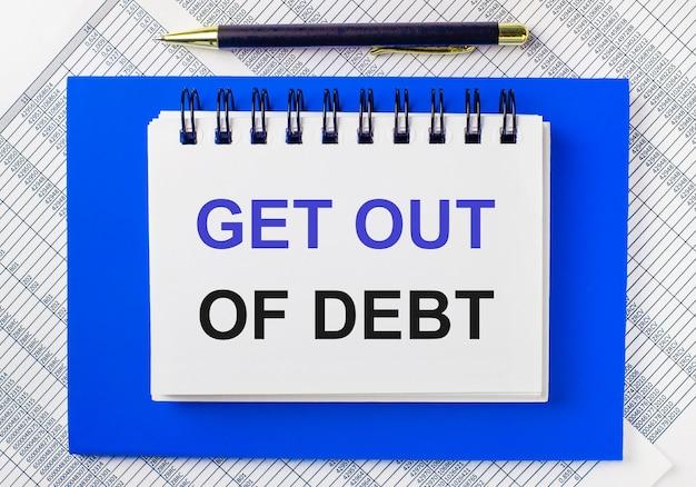 Tegen de achtergrond van rapporten op het bureaublad, een blauw notitieblok. het heeft een pen en een wit notitieboekje met de tekst get out of debt. bedrijfsconcept