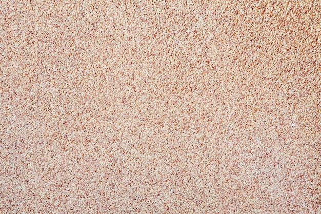 Tegen de achtergrond van verspreid zand klein grind, een stenen kruimel. het patroon van een oppervlak van een muur, lichte kleur