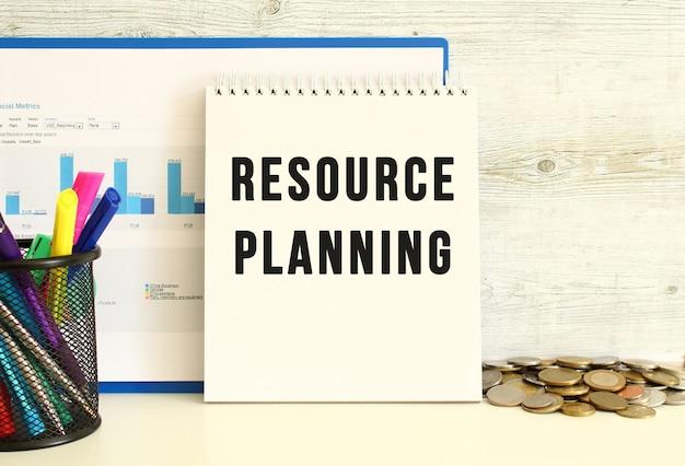Tegen de muur leunt een notitieboekje met de tekst resource planning met een map met grafieken.