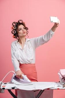 Tegen een roze muur werkt een mooie huisvrouw met een haarkrultang kleren op de strijkplank en neemt een selfie aan de telefoon