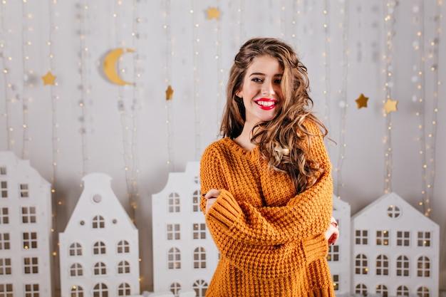 Tegen kartonnen warme decoraties in de vorm van slingers en witte huizen, mooie bruinharige vrouw in mooie, warme trui poseren