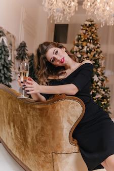 Tegen kerstversieringen, kerstbomen en speelgoed poseert lieve en gepassioneerde vrouw zittend op gouden fauteuil, onder kristallen kroonluchter