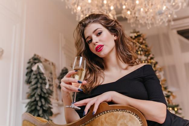 Tegen versierde kerstbomen, op dure stoel, achterover leunend, zittende jonge en aantrekkelijke vrouw 25 jaar oud, met glas champagne in haar handen en met gepassioneerde blik
