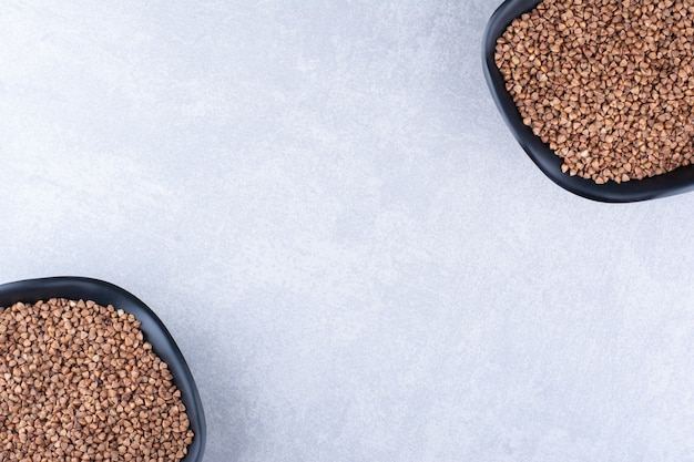Tegenover elkaar geplaatste kommen rauwe boekweit op marmeren oppervlak