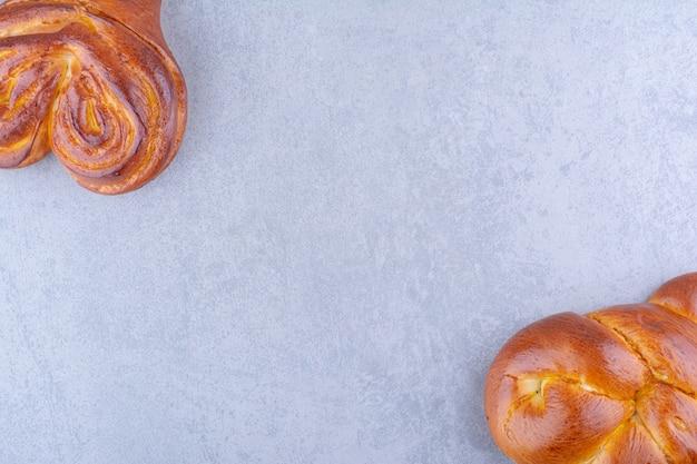 Tegenover elkaar geplaatste zoete hartjesbroodjes samengebundeld op een marmeren oppervlak