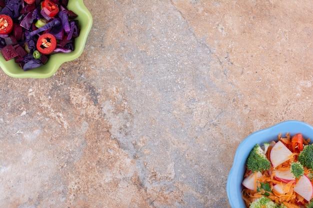 Tegenover elkaar uitgelijnde kommen met verschillende salades weergegeven op een marmeren oppervlak