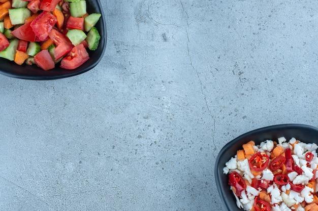 Tegenover elkaar uitgelijnde saladeschalen op marmer.
