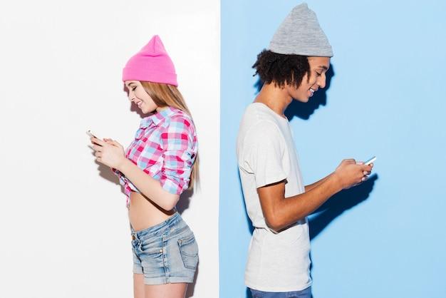 Tegenpolen trekken elkaar aan. funky jong stel dat mobiele telefoons vasthoudt en rug aan rug staat terwijl ze tegen een kleurrijke achtergrond staan