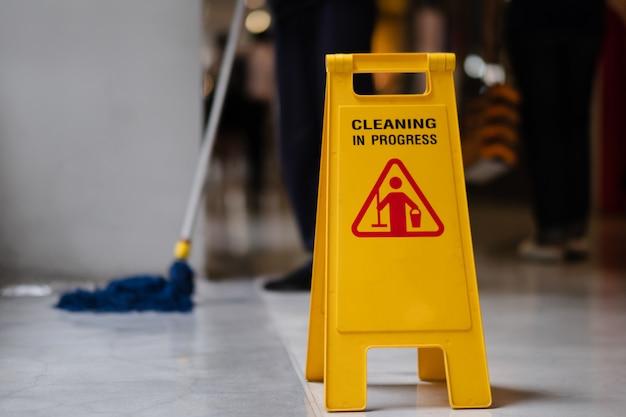 Teken dat waarschuwing van voorzichtigheids natte vloer in luchthaven toont.