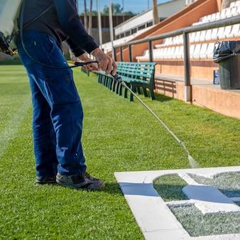 Teken letters op het gras in het wit over een sjabloon. de naam van het voetbalveld op het gras
