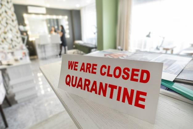 Teken met de waarschuwing dat we tijdens de uitbraak van de covid-19 coronovirus pandemie in quarantaine zijn gesloten. quarantaine in een schoonheidssalon of kapsalon. problemen van kleine bedrijven.