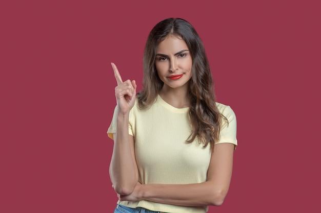Teken omhoog. overtuigende knappe jonge vrouw met vinger opgewekt in gele t-shirt camera kijken