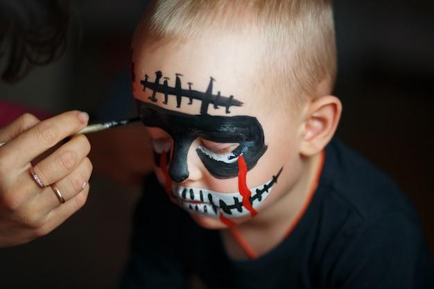 Teken op het gezicht van de jongen. emotioneel portret met een enge zombie op zijn gezicht