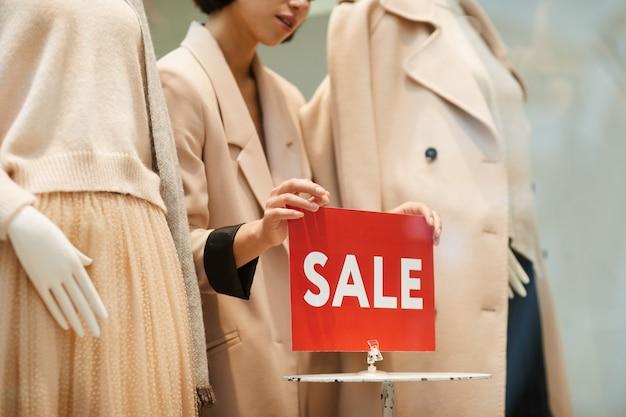 Teken van de vrouwen het hangende verkoop in kledingsopslag