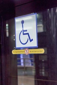 Teken voor gehandicapten op een glazen deur close-up