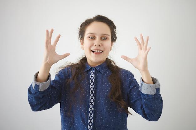 Tekenen, gebaren en lichaamstaal concept. geïsoleerde shot van vrolijke mooie brunette 13-jarige meisje breed glimlachend