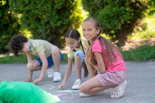 Tekenen met kleurpotloden. langharig lachend meisje in roze t-shirt gehurkt met krijt in de buurt van haar tekenvrienden in het park op zonnige dag