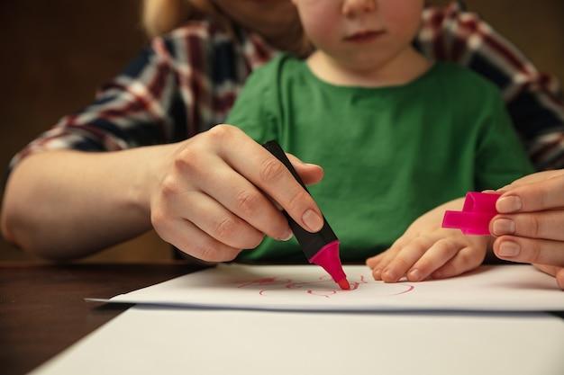 Tekenen met kleurrijke markeringen. close-up shot van de handen van vrouwen en kinderen die verschillende dingen samen doen. familie, huis, onderwijs, jeugd, liefdadigheidsconcept. moeder en zoon of dochter, studeren.